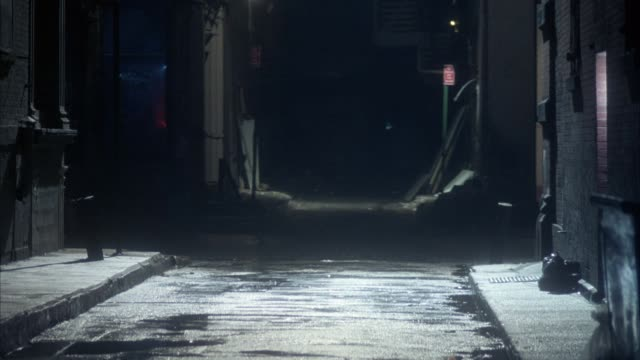 medium angle of center of alley with moonlight in middle section. alley between brick or concrete buildings. dark shot. - alley stock videos & royalty-free footage
