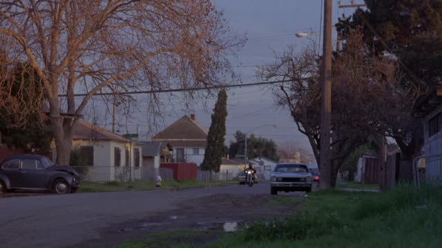 """tracking shot of man riding black honda shadow motorcycle on suburban or residential street from right to left, see building at end with sign that reads """"ravens,"""" palm tree next to building. - honda bildbanksvideor och videomaterial från bakom kulisserna"""