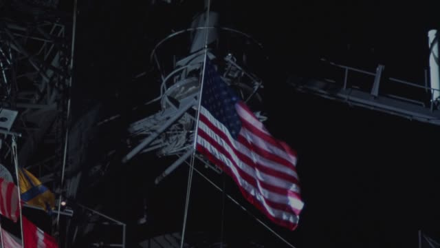 pan up of american flag on us navy ship as american flag is raised. spotlights shine on and move around flag. could be an aircraft carrier. military. - warship stock videos & royalty-free footage