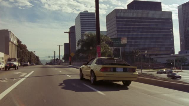 medium angle tracking shot of yellow sports car, possibly camaro, traveling away from pov around city streets of century city. see  multi-story office buildings, trees, and telephone poles along sides of street. see bus, trucks, and cars traveling on stre - chevrolet stock videos & royalty-free footage