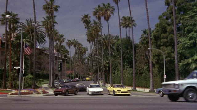 pan left to right of yellow sports car, possibly camaro, crossing palm tree lined city street intersection. see cars parked on one side of street. see beverly hills hotel at frame left, dense green foliage at frame right. see cars pass from frame left to - palm tree stock videos & royalty-free footage
