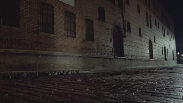 medium angle establish of brick warehouse and cobblestone road beside it. see bars on windows. see light reflected on brick and stone surfaces. see car with headlights on heading towards pov enter frame right as clip ends. could be alley. - cobblestone stock videos & royalty-free footage