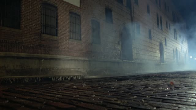 medium angle establish of brick warehouse and cobblestone road beside it. see bars on windows. see light reflected on brick and stone surfaces. see smoke or fog blowing down road from frame right to left. see leaf blown onto road. - kopfsteinpflaster stock-videos und b-roll-filmmaterial