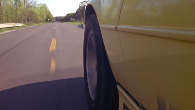 close angle of front wheel of yellow car traveling away from pov on rural area highway. see wheel and car slow and stop at end of clip. see pavement and yellow stripes of highway. see shadows stretch across highway. see trees line both sides of road. coul - 1998 stock videos & royalty-free footage
