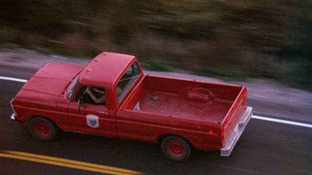 aerial tracking shot of red pickup truck on two lane road through countryside with plains or vegetation on sides. pulls back as truck passes to left. - truck stock videos & royalty-free footage