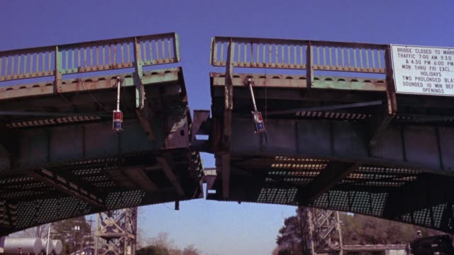 pan up of drawbridge as it splits opens or rises in center. neg cuts. - drawbridge stock videos & royalty-free footage