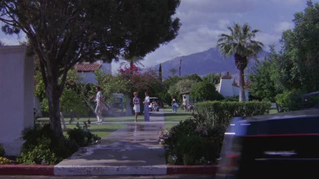 high angle down. man in golf attire walks away from camera. motoracde of limousines drive by left to right. front limo has u.s. and california flag. camera rises to show community of people walking, talking. golf cart goes by. see palm trees and red tile - golf cart stock videos and b-roll footage