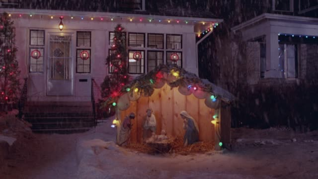 zoom in on nativity scene in snow covered front yard of one story white house. see christmas lights, decorations and snowing. - キリスト降誕点の映像素材/bロール