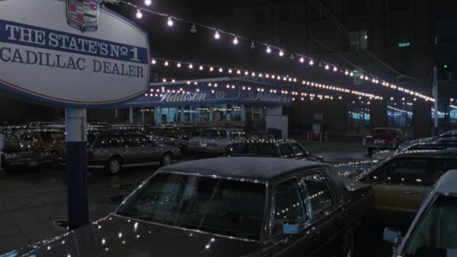 "medium angle of cadillac dealer lot. white van with headlights on drives through lot and exits frame left. see sales office, strings of lights hanging over parked cadillacs, sign reads ""the states no. 1 cadillac dealer."" - car showroom stock videos & royalty-free footage"