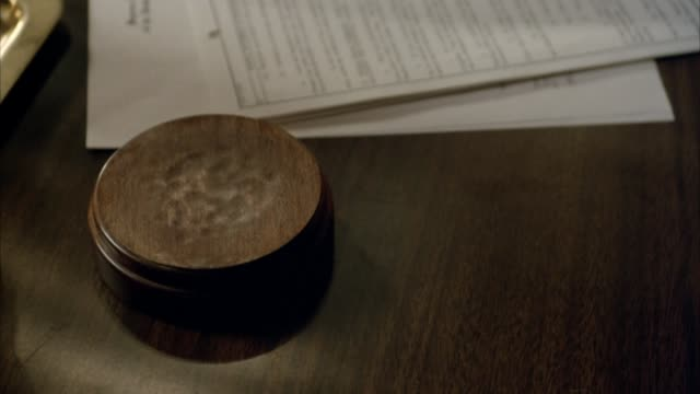 vidéos et rushes de close angle of wood block sitting on table next to paper documents. see gavel move down from left and hit block three times. pan up, see hand holding gavel and figure wearing suit. books on table in background. probably judge or lawyer in chambers. - juge