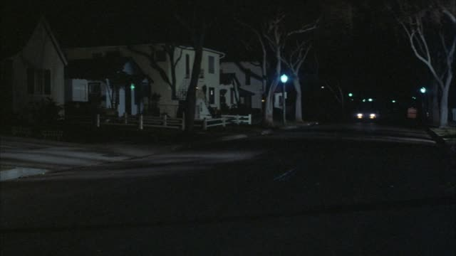 medium angle neighborhood street. see car, headlights on in left lane moving toward pov. see middle class homes at left. - headlight stock videos & royalty-free footage