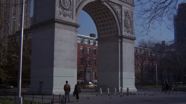 vidéos et rushes de medium angle washington park arch at washington square park. red brick apartment building in background, people walk in park.  see flock of pigeons fly up into sky. blue sky, sun shining. greenwich village. - medium group of animals