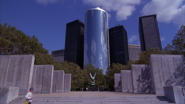 establish wide angle of 17 state street office building as seen from the east coast war memorial in battery park, located in lower manhattan. the memorial consists of a large bronze sculpture of an eagle flanked on each side by four granite walls. see ste - other stock videos & royalty-free footage