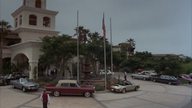 stockvideo's en b-roll-footage met medium angle red tile roof, spanish style building. see circular drive, arched and covered entrance. fountain in front surrounded by palm trees, flowers. american flag on pole. porsche, rolls royce, mercedes benz convertible parked on drive. could be reso - image