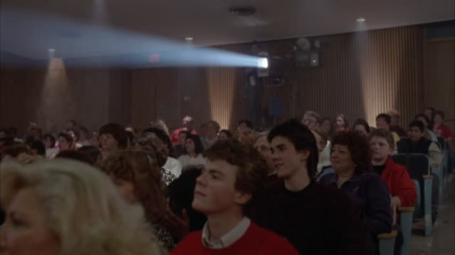 medium angle crowd of seated people. see blue light from back of room. could be auditorium or theater. see crowd moving and clapping hands in seats. could be concert or performance. - auditorium stock videos & royalty-free footage