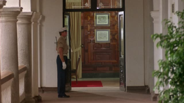 vidéos et rushes de medium angle of military guard standing outside doorway on balcony. could be embassy, military hospital, or consulate. - amérique du sud