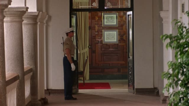 medium angle of military guard standing outside doorway on balcony. could be embassy, military hospital, or consulate. - embassy stock videos & royalty-free footage