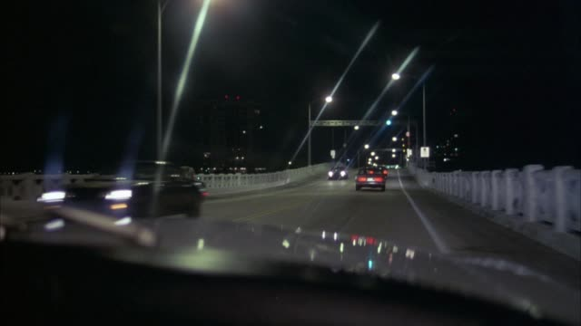 MEDIUM ANGLE DRIVING POV OVER BRIDGE WITH TWO LANES AND WHITE RAILINGS,  LIT STREET LAMPS ON BOTH SIDES. SEE CARS MOVING ON EITHER SIDE. POV MOVES OVER TOP OF BRIDGE.  CAR IN LEFT LANE TURNS IN FRONT OF POV.