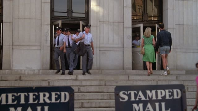 medium angle of post office with postal workers exiting from doors and climbing down stairs. workers appear to be leaving to go on route. - postamt stock-videos und b-roll-filmmaterial