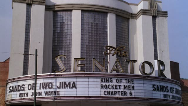 "medium angle of ""the senator"" movie theater. see movie titles ""sands of iwo jima"" and ""king of the rocket men chapter 6"" on theater marquee. - colour image stock videos & royalty-free footage"