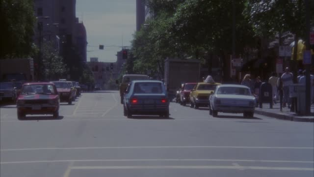 medium angle of cars driving down street through urban area. suddenly see taxi swerve into intersection from opposite direction and cause cars to swerve out of way. - 1989 stock videos & royalty-free footage