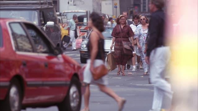 medium angle of crowds of people crossing street in crosswalk. see people stop to let cars pass. - 1990年点の映像素材/bロール