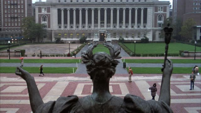 wide angle of columbia university quad and campus area. pov is from behind statue of roman goddess, minerva. ivy league college. - minerva 個影片檔及 b 捲影像