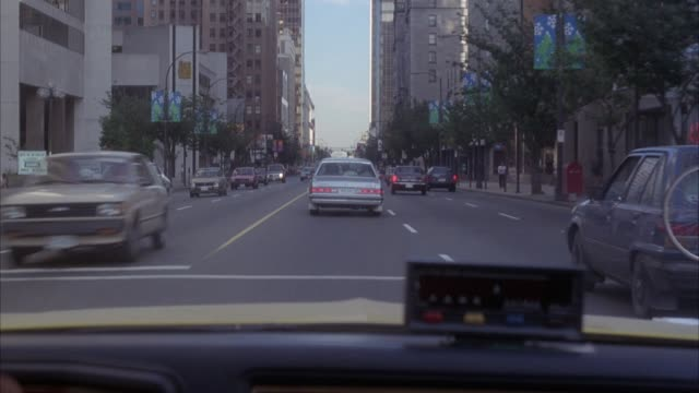 medium angle driving pov along city street, see meter in pov. probably taxi. pov in left lane, switches to middle lane. traffic  moving in both directions. see high rise buildings along street, trees on sidewalks. pov stops at red light intersection. neg - red light stock videos & royalty-free footage