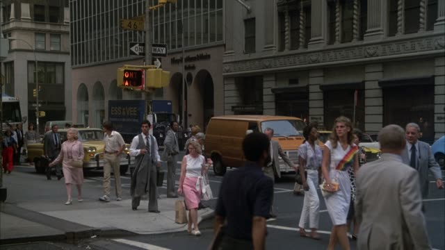 "medium angle of city street at intersection. see city buses, taxis drive by. pedestrians on sidewalk, walk along crosswalk. high rise buildings line street. see yellow cab turn left at intersection, stop in front of hotel. see ""the roosevelt"" at top of aw - 1989 stock videos & royalty-free footage"