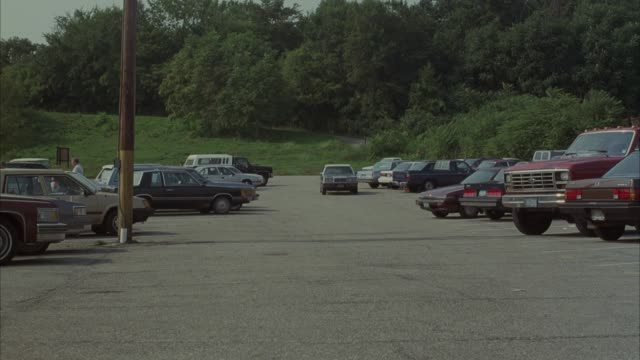 medium angle of parking lot, green trees in background on hill. see chrysler convertible with cloth top approaching pov, parked cars on either side. car turns left and crash into front of  red porsche. chrysler car. - convertible top stock videos & royalty-free footage