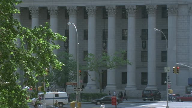 medium angle of white brick multi story building,  corinthian columns supporting. could be city hall or government building. see city street in front, traffic at intersection, and pedestrians on sidewalk. - korinthisch stock-videos und b-roll-filmmaterial