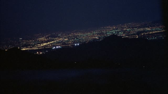 panoramic driving pov of city from distance. city lies in valley, see bright lights of city. could be on mountain or hills looking into valley. bushes and trees in pov. - valley stock videos & royalty-free footage