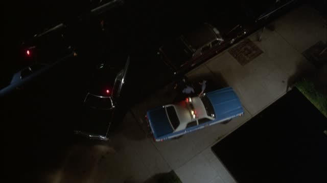 vídeos de stock, filmes e b-roll de high angle down of new york city street. police car with red light flashing on top, turn at intersection and drive onto sidewalk behind blue and white nypd police car, lights flashing. other police cars drive up, officers exit and run into building. could - 1980 1989