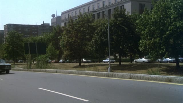 medium angle of cars driving down city street. see trees in center divide and tall office buildings in background. see small red convertible sports car possibly late 1970's drive down street towards pov. camera pans left to right, see car drive away from - オープンカー点の映像素材/bロール