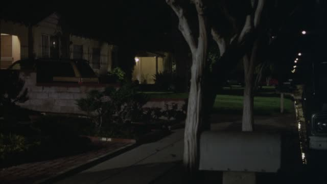 medium angle establish of suburban street. see one-story house on frame left. see possible jeep or suv parked in driveway. see trees in sidewalk and streetlights lit. - suburban stock videos & royalty-free footage