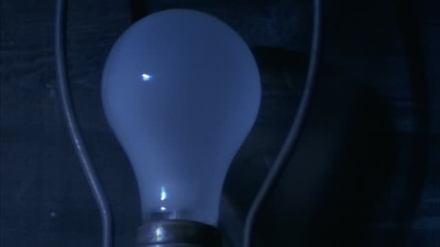 close angle of light bulb with lamp harp. see blue flashes of light. see light bulb illuminate. see wooden panel in background. - light bulb stock videos and b-roll footage
