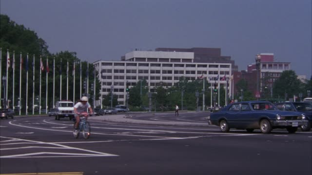 medium angle of city street, see multi-story building in background, could be office or government building.  see line of flags at frame left, cars coming towards pov. camera pans left to right tracking white and blue police van. see large building in bac - 1990 stock videos & royalty-free footage