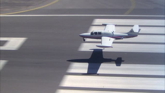 vidéos et rushes de aerial of small white private jet aircraft flying over fields. see jet touchdown on runway, possible airport. see jet take off and fly away from pov above fields towards blue sky. - piste d'envol