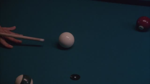 PAN LEFT TO RIGHT OF POOL TABLE. SEE CUE STICK HIT CUE BALL AND MOVE DOWN TABLE TO FRAME RIGHT, SEE CUE BALL HIT 13 BALL, MISS POCKET AND BOUNCE OFF TO RAILS.