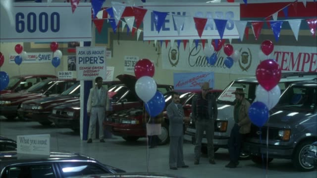 vídeos de stock e filmes b-roll de medium angle of car dealership. see cars and vans parked on either side of aisle. see signs, banners, flags, abd balloons hanging in room. see car salesman talking to two men with cowboy hats. - stand de carros