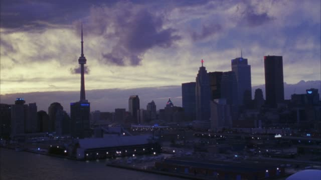 aerial shot of toronto skyline at sunset. see downtown including cn tower. see cloudy sky. frame pans slightly right at end. - toronto stock videos & royalty-free footage