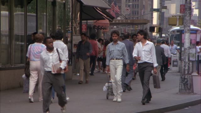 medium angle of pedestrians walking along busy city sidewalk downtown. see van drive from left to right in front of pedestrians. - 1993 bildbanksvideor och videomaterial från bakom kulisserna