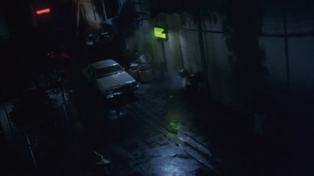 high angle down on dark alley or street. see steam vent from side of building. see white car parked, boxes, illuminated signs on walls of businesses, and rain puddled pavement. - dampf stock-videos und b-roll-filmmaterial