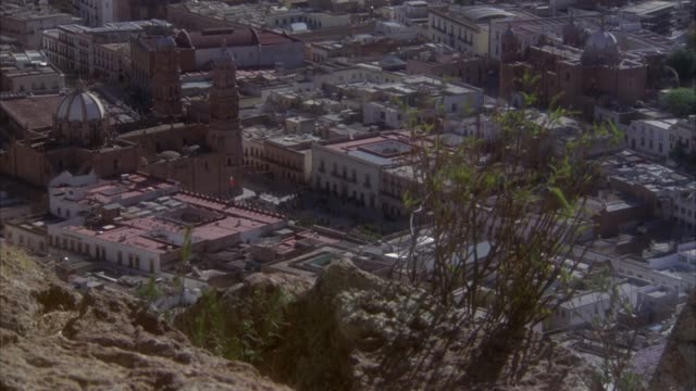 pan down of old buildings of mexican city. see red tile roofs on many buildings. see possible cathedral. see wind blow plant on mountain outcrop in foreground. could be south american town. could be italian town. - mexican american stock videos & royalty-free footage