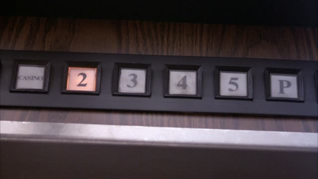 """close angle of elevator floor indicator display with """" casino,"""" """"2,"""" """"3,"""" """"4,"""" """"5,"""" and """"p"""" labeled on individual glass squares. pov looking up at these lights. see the light go from """"casino"""" all the way to """"4"""" before lights in elevator begin to flicker a - casino floor stock videos & royalty-free footage"""