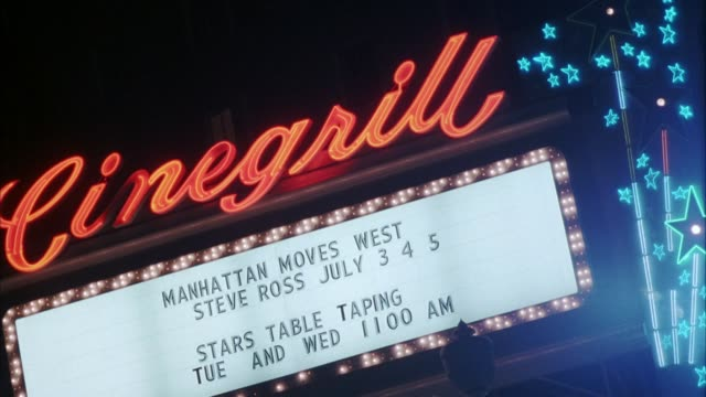 "up angle of neon sign with ""cinegrill"" on top and shooting stars on right side. marquee with flashing lights racing around it announces ""manhattan moves west steve ross july 3 4 5"" and ""stars table taping wed 11 am."" hollywood blvd. - 1990 stock videos & royalty-free footage"