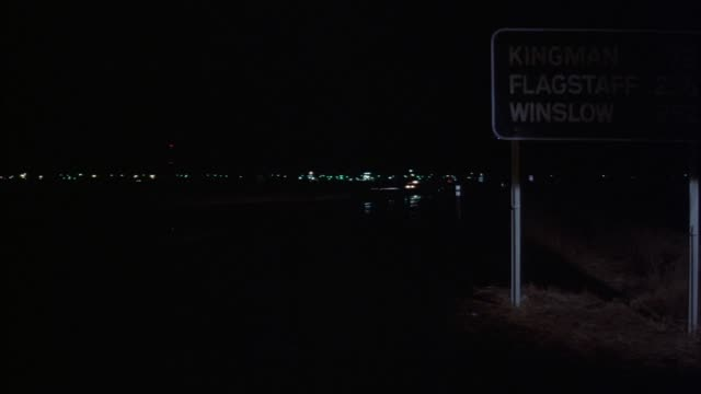 """wide angle of deserted highway with lights of distant community far in background. distance marker sign with """"kingman 75 flagstaff 256 winslow 292"""" on it at frame right. see car emerge from frame left traveling to frame right. see bus with headlights on e - kingman arizona stock videos & royalty-free footage"""