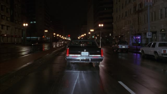 vídeos de stock, filmes e b-roll de tracking shot of black 1984 cadillac fleetwood sedan driving down city streets away from pov. see lights shining from police car in background. see office buildings on each side of street. - cadillac