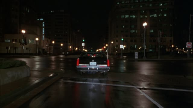 tracking shot of black 1984 cadillac fleetwood sedan driving down city streets away from pov. see lights shining from police car in background. see office buildings on each side of street. - キャデラック点の映像素材/bロール