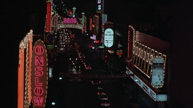 "est. medium angle of reno city streets. see cars drive down street in both directions. see lighted neon sign that says ""reno"" and other neon signs on hotels and casinos along both sides of street. see pedestrians walk in streets in background. - nevada stock videos & royalty-free footage"
